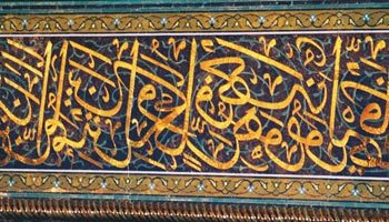 Gold inlaid Quranic calligraphy adorns the inner walls of the Grand Mosque in Oman's Capital Territory.