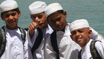 Potential Omani leaders of tomorrow – schoolboys, their book bags strapped to their backs, returning home from a day's study in Qumzar, a small seaside village tucked into a cove adjacent to the Hormuz Strait.