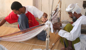Omani village pitweavers work their magic in producing one of the multi-colored headdresses worn by Omanis.