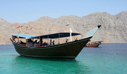A traditional Arab sailing dhow, fashioned from wood and crafted by hand in the manner of Omani shipwrights and mariners of yesteryear, plies the sea in and out of the Hormuz Strait, the world's most strategically vital waterway.
